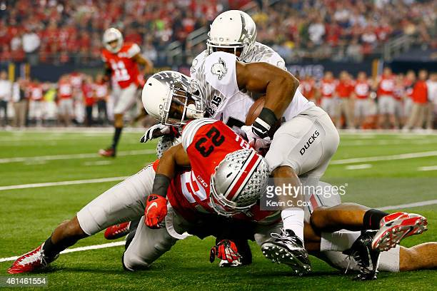 Running back Royce Freeman of the Oregon Ducks is hit by safety Tyvis Powell of the Ohio State Buckeyes during the College Football Playoff National...