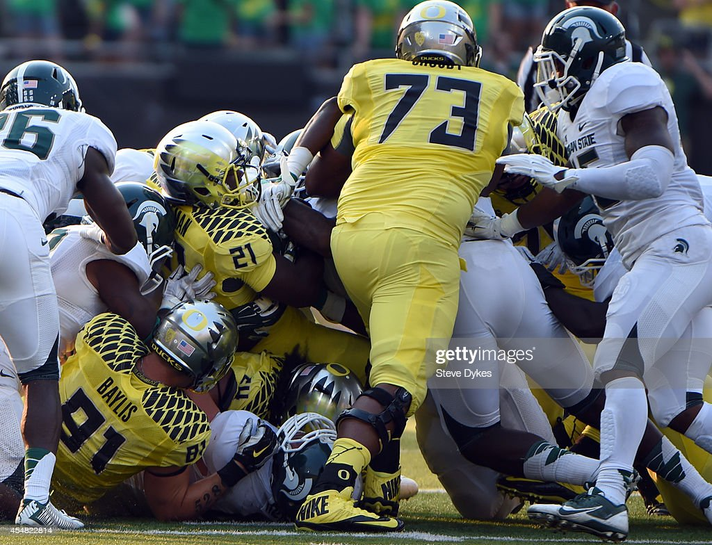 Running back Royce Freeman #21 of the Oregon Ducks runs for a first down during the third quarter of the game against the Michigan State Spartans at Autzen Stadium on September 6, 2014 in Eugene, Oregon. Oregon won the game 46-27.
