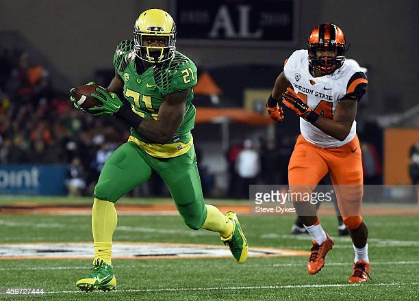 Running back Royce Freeman of the Oregon Ducks runs the ball for a touchdown as linebacker Jabral Johnson of the Oregon State Beavers gives chase...