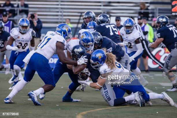 Running back Russell Booze of the Nevada Wolf Pack is taken down by San Jose State Spartans players while attempting a run at Mackay Stadium on...
