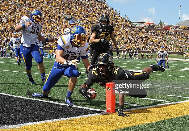 Running back Russell Hansbrough of the Missouri Tigers dives into the end zone for a touch down against the Nick Mears of the South Dakota State...