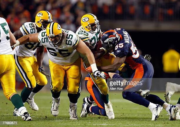 Running back Ryan Grant of the Green Bay Packers holds onto the ball as he is hit by linebacker DJ Williams of the Denver Broncos at Invesco Field at...