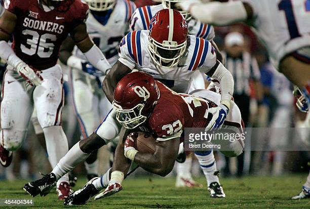 Running back Samaje Perine of the Oklahoma Sooners is brought down by defensive back Xavier Woods of the Louisiana Tech Bulldogs August 30, 2014 at...