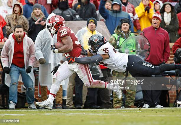 Running back Samaje Perine of the Oklahoma Sooners is hit by linebacker Chad Whitener of the Oklahoma State Cowboys December 3 2016 at Gaylord...
