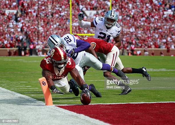 Running back Samaje Perine of the Oklahoma Sooners reaches for a touchdown as he is hit by defensive back Dante Barnett of the Kansas State Wildcats...
