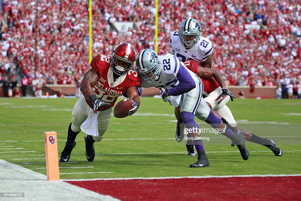 Running back Samaje Perine #32 of the Oklahoma Sooners reaches for a touchdown as he is chased by defensive back Dante Barnett #22 and defensive back Kendall Adams #21 of the Kansas State Wildcats October 15, 2016 at Gaylord Family-Oklahoma Memorial Stadium in Norman, Oklahoma. Oklahoma defeated Kansas State 38-17.