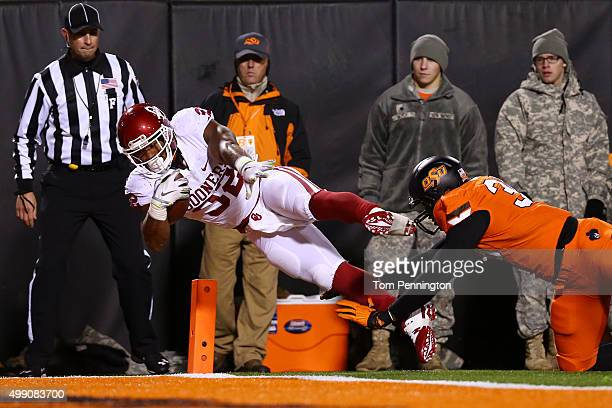 Running back Samaje Perine of the Oklahoma Sooners scores a second quarter touchdown past defensive end Emmanuel Ogbah of the Oklahoma State Cowboys...
