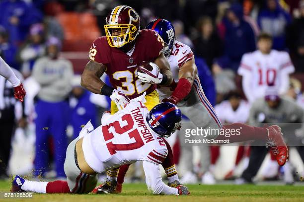 Running back Samaje Perine of the Washington Redskins is tackled by free safety Darian Thompson and defensive end Olivier Vernon of the New York...