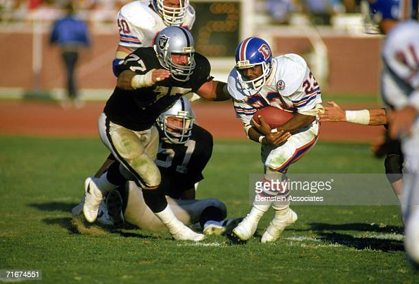 Running back Sammy Winder of the Denver Broncos carries the ball as Lyle Alzado of the Los Angeles Raiders moves to tackle during a 1984 season game...