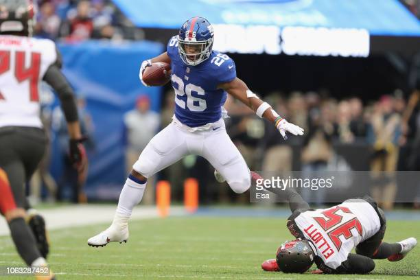 Running back Saquon Barkley of the New York Giants carries the ball as he jumps over cornerback Javien Elliott of the Tampa Bay Buccaneers for a...