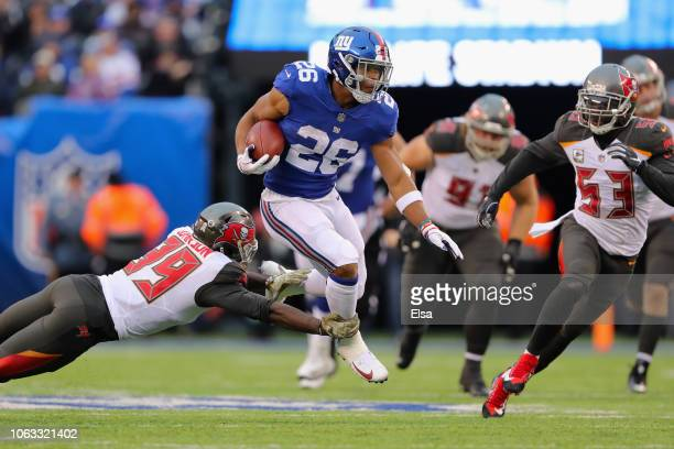 Running back Saquon Barkley of the New York Giants carries the ball for a 23-yard gain against safety Isaiah Johnson and linebacker Adarius Taylor of...