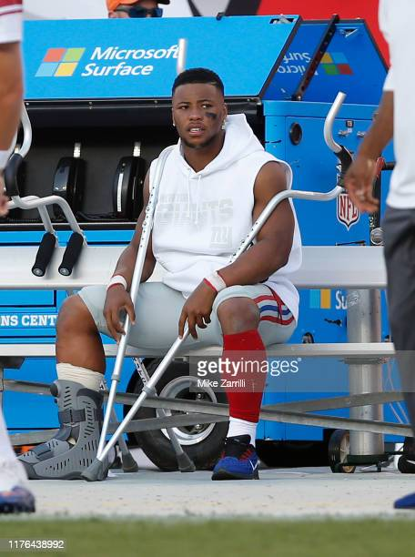 Running back Saquon Barkley of the New York Giants sits on the bench with crutches and a boot after injuring his ankle in the first half during the...