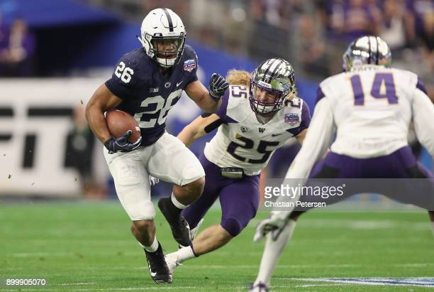 Running back Saquon Barkley of the Penn State Nittany Lions rushes the football past linebacker Ben BurrKirven of the Washington Huskies during the...