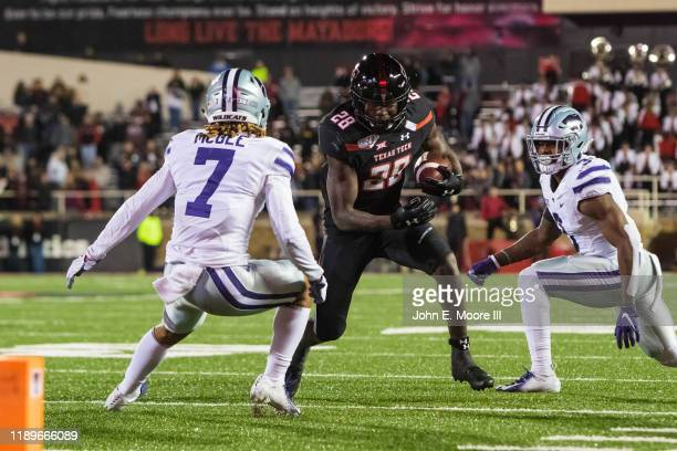 Running back SaRodorick Thompson of the Texas Tech Red Raiders runs the ball against cornerback Kevion McGee and linebacker Elijah Sullivan of the...
