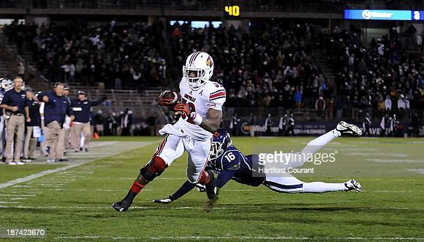 Running back Senorise Perry of Louisville gets past cornerback Byron Jones of Connecticut for a touchdown in the second quarter at Rentschler Field...