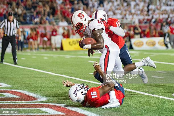 Running back Shadrach Thornton of the North Carolina State Wolfpack runs the ball over cornerback Nigel Lawrence of the South Alabama Jaguars for a...