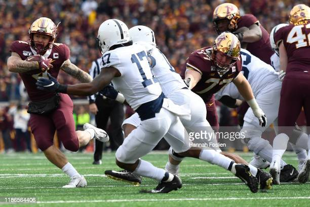 Running back Shannon Brooks of the Minnesota Golden Gophers rushes in front of safety Garrett Taylor of the Penn State Nittany Lions during the...