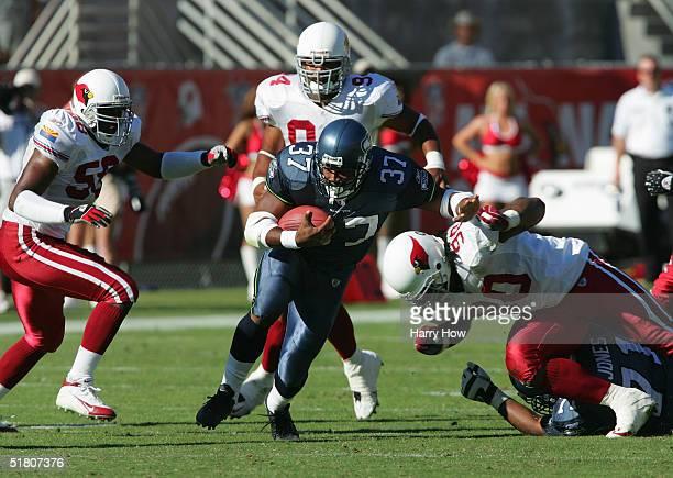 Running back Shaun Alexander of the Seattle Seahawks evades defensive end Peppi Zellner, defensive tackle Darnell Dockett, and linebacker Karlos...