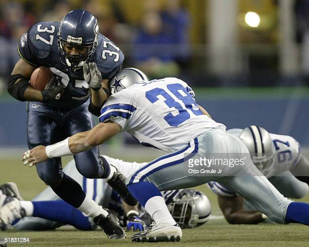 Running back Shaun Alexander of the Seattle Seahawks rushes against Lynn Scott of the Dallas Cowboys on December 6, 2004 at Qwest Field in Seattle,...