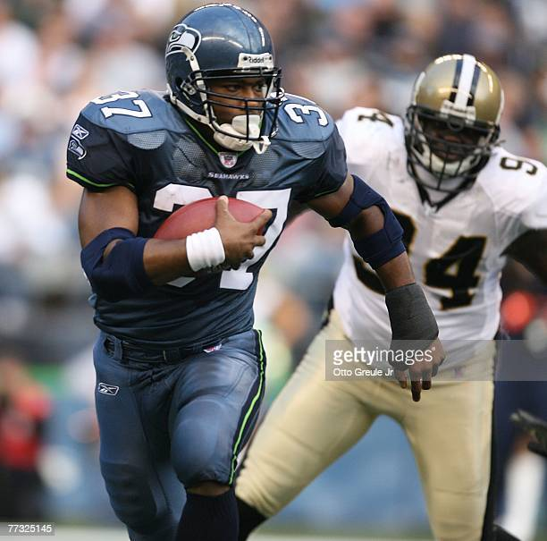 Running back Shaun Alexander of the Seattle Seahawks rushes against Charles Grant of the New Orleans Saints at Qwest Field on October 14 2007 in...