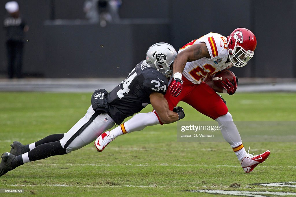 Running back Shaun Draughn #20 of the Kansas City Chiefs is tackled by strong safety Mike Mitchell #34 of the Oakland Raiders during the first quarter at O.co Coliseum on December 16, 2012 in Oakland, California.