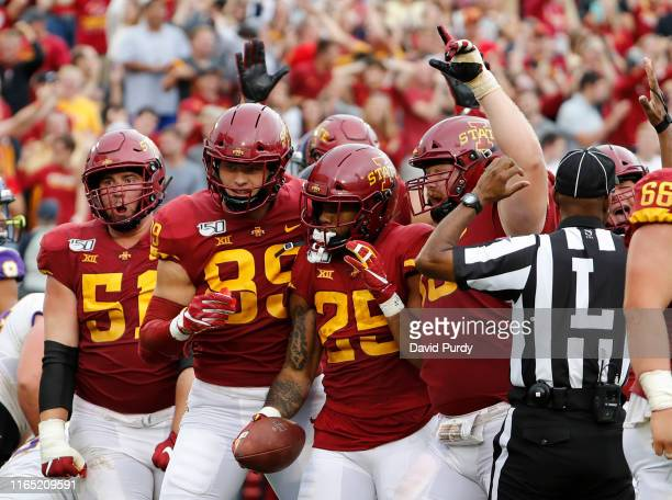 Running back Sheldon Croney Jr #25 of the Iowa State Cyclones center celebrates with teammates after scoring the winning touchdown in triple overtime...