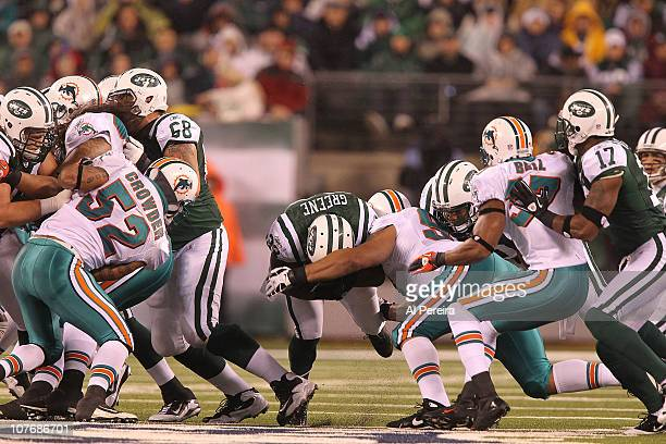 Running Back Shonn Greene of the New York Jets is stpped by the defense of the Miami Dolphins at New Meadowlands Stadium on December 12, 2010 in East...