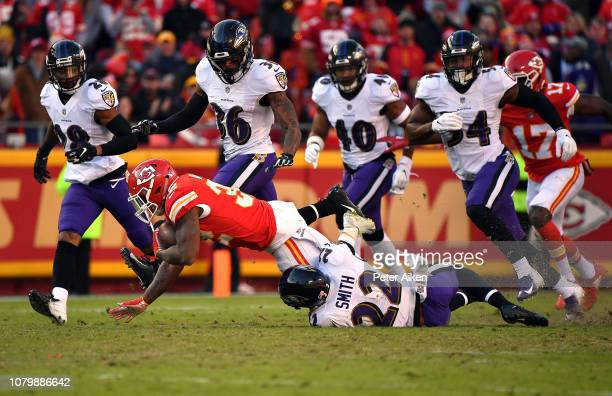Running back Spencer Ware of the Kansas City Chiefs carries the ball as cornerback Jimmy Smith of the Baltimore Ravens defends during the game at...