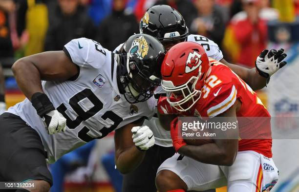 Running back Spencer Ware of the Kansas City Chiefs gets tackled by defensive end Calais Campbell of the Jacksonville Jaguars and defensive end Dante...