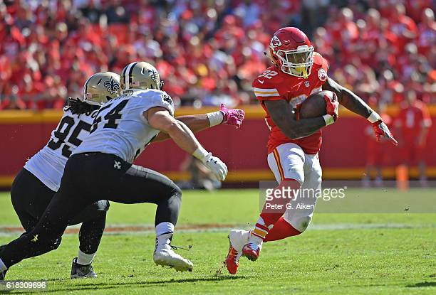 Running back Spencer Ware of the Kansas City Chiefs rushes past defenders Nate Stupar and Tyeler Davison of the New Orleans Saints during the second...