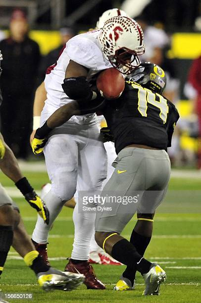 Running back Stepfan Taylor of the Stanford Cardinal fumbles the ball as he is hit by cornerback Ifo EkpreOlomu of the Oregon Ducksduring the third...