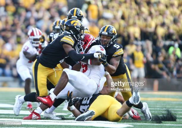 Running back Stephen Carr of the Indiana Hoosiers is brought down during the second half by defensive back Reggie Bracy and linebacker Jestin Jacobs...