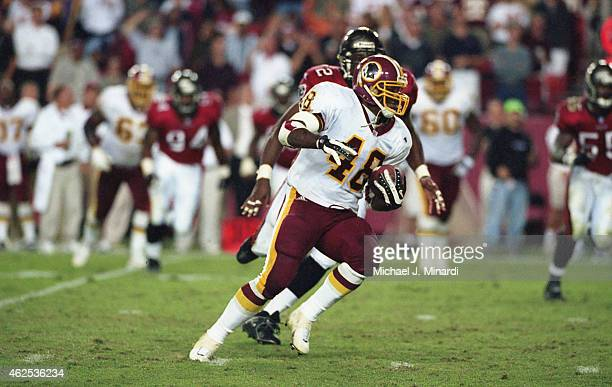 Running Back Stephen Davis of the Washington Redskins is running with the ball and is being chased for a tackle by Defensive Left End Chidi Ahanotu...