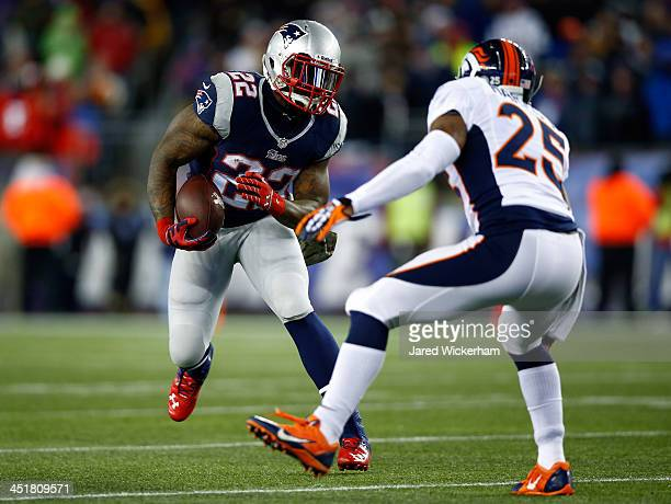 Running back Stevan Ridley of the New England Patriots carries the ball as cornerback Chris Harris of the Denver Broncos defends during a game at...