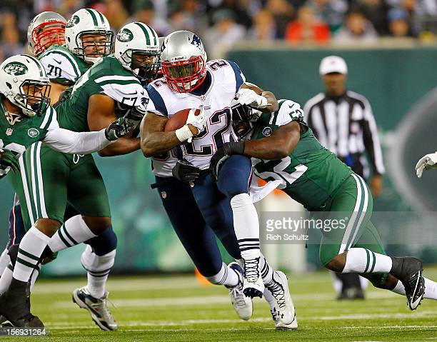 Running back Stevan Ridley of the New England Patriots fights off Bart Scott and David Harris of the New York Jets during the first half of a game at...