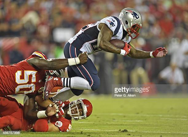 Running back Stevan Ridley of the New England Patriots gets tackled from behind by linebackers Justin Houston and Josh Mauga of the Kansas City...