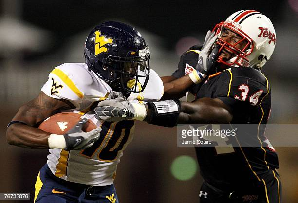 Running back Steve Slaton of the West Virginia Mountaineers carries the ball as he stiffarms Dave Philistin of the Maryland Terrapins during the...