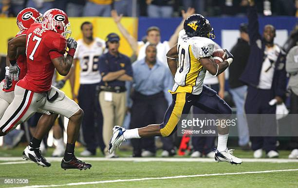 Running back Steve Slaton of the West Virginia Mountaineers runs for a 52 yard touchdown against the defense of the Georgia Bulldogs during 4th...