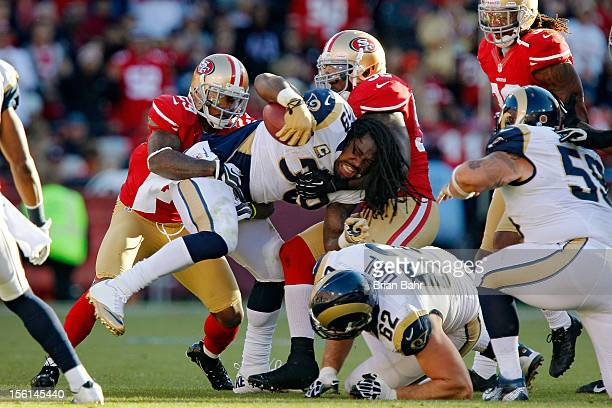 Running back Steven Jackson of the St Louis Rams gets tackled by cornerback Chris Culliver and linebacker Patrick Willis of the San Francisco 49ers...