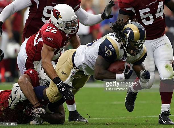 Running back Steven Jackson of the St Louis Rams is tackled by Matt Ware of the Arizona Cardinals and another defender on September 24 2006 at...
