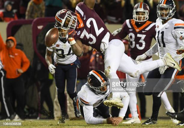 Running back Steven Peoples of the Virginia Tech Hokies has the ball knocked loose by safety Joey Blount of the Virginia Cavaliers in the second half...