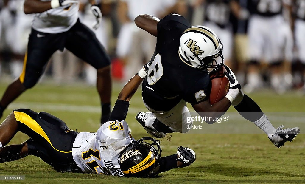 Running back Storm Johnson #8 of the Central Florida Knights is tackled by defender Emmanuel Johnson #12 of the Southern Mississippi Golden Eagles during the game at Bright House Networks Stadium on October 13, 2012 in Orlando, Florida.