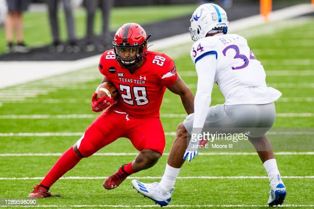 Running back Tahj Brooks of the Texas Tech Red Raiders runs the ball against safety Nate Betts of the Kansas Jayhawks during the first half of the...