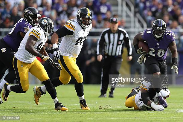 Running back Terrance West of the Baltimore Ravens carries the ball against outside linebacker Jarvis Jones of the Pittsburgh Steelers in the first...
