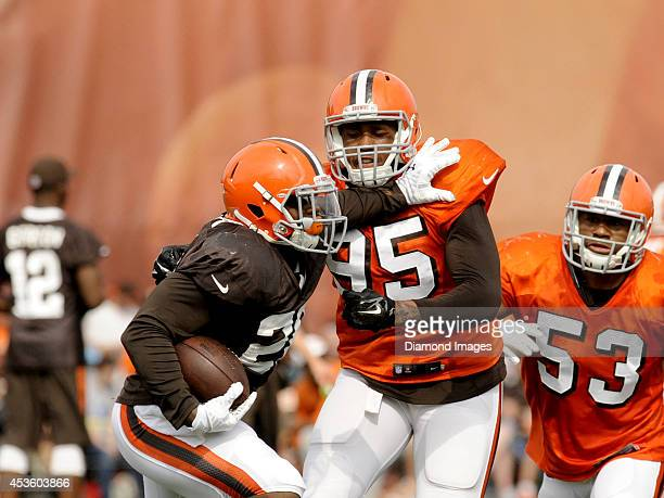 Running back Terrence West of the Cleveland Browns stiff arms defensive end Armonty Bryant during a training camp practice on August 12 2014 at the...