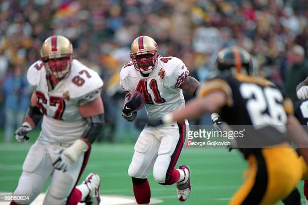 Running back Terry Kirby of the San Francisco 49ers runs behind the blocking of offensive lineman Chris Dalman during a game against the Pittsburgh...