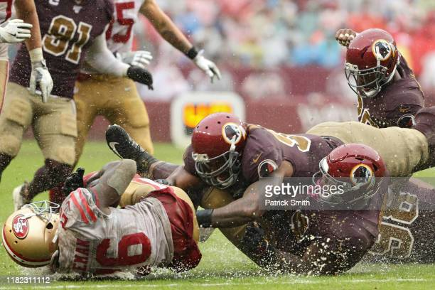 Running back Tevin Coleman of the San Francisco 49ers is tackled by Washington Redskins defenders during the fourth quarter at FedExField on October...