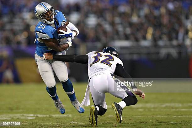 Running back Theo Riddick of the Detroit Lions eludes defensive back Eric Weddle of the Baltimore Ravens during the first half in their preseason...