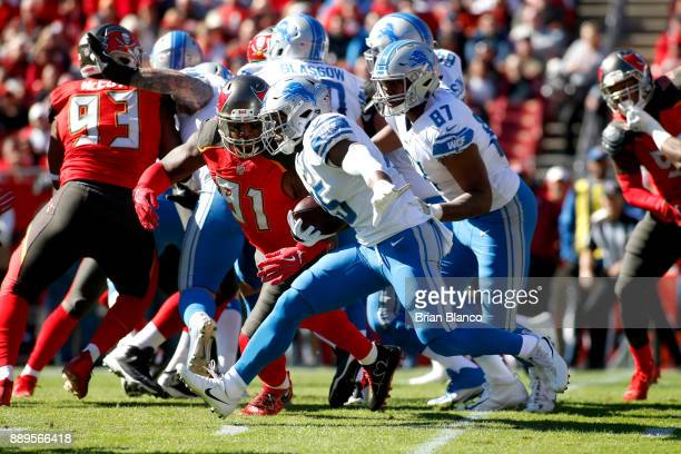 Running back Theo Riddick of the Detroit Lions gets pressure from defensive end Robert Ayers of the Tampa Bay Buccaneers during a carry in first...