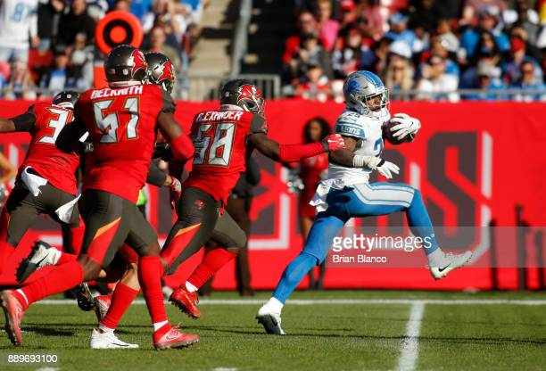 Running back Theo Riddick of the Detroit Lions slips a tackle by middle linebacker Kwon Alexander of the Tampa Bay Buccaneers as he rushes for a...